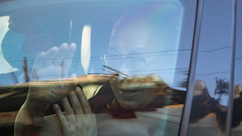 Tibetan spiritual leader the Dalai Lama waves from inside his car as he leaves the Zonal Hospital after receiving a COVID-19 vaccine in Dharmsala, India, Saturday, March 6, 2021. (AP Photo/Ashwini Bhatia)
