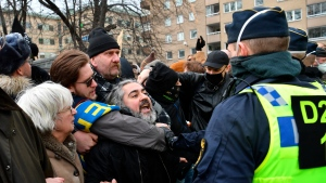 Anti-lockdown protesters face police during a demonstration against the coronavirus restrictions in Stockholm Saturday March 6, 2021. The protest was disbanded by police due to lack of permit for the public gathering. (Henrik Montgomery / TT via AP)