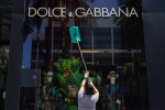Dulce Gonzalez cleans the front window of Dolce & Gabbana on Rodeo Drive Tuesday, May 19, 2020, in Beverly Hills, Calif. (AP Photo/Ashley Landis)