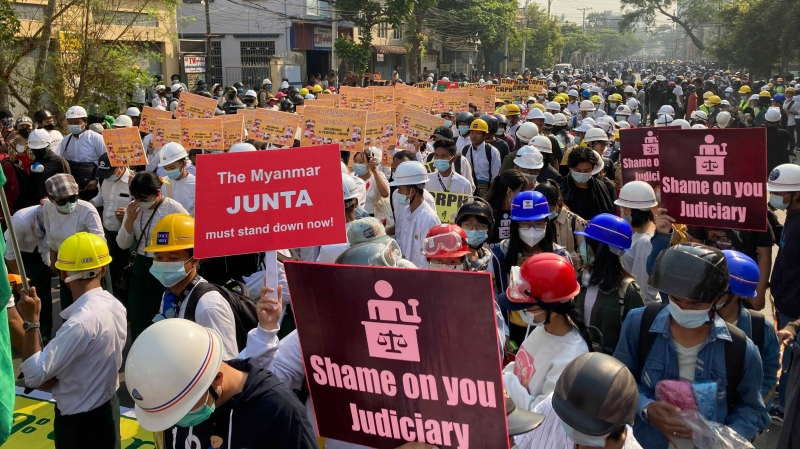 Health and medical students hold placard while march on main road during a demonstration in Mandalay, Myanmar, Sunday, March 7, 2021. (AP Photo)