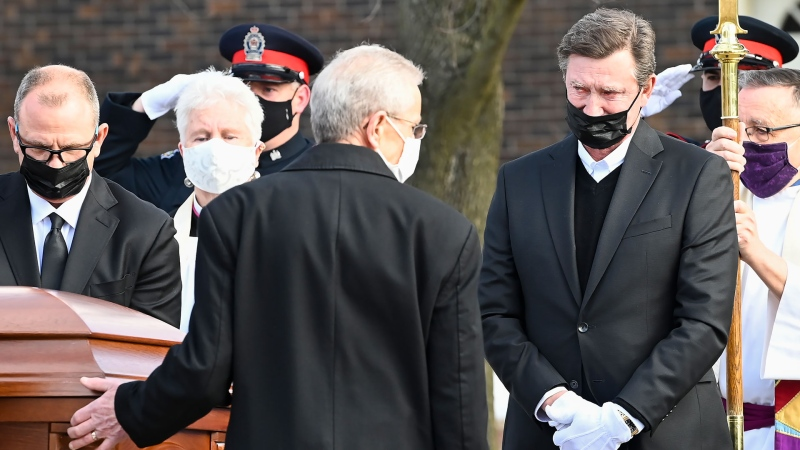 Hockey hall-of-fame legend Wayne Gretzky, right, watches the casket of his father, Walter Gretzky, as it is carried from the church during a funeral service in Brantford, Ont., Saturday, March 6, 2021. Walter Gretzky, also know as Canada's hockey dad, was 82 years-old. THE CANADIAN PRESS/Nathan Denette
