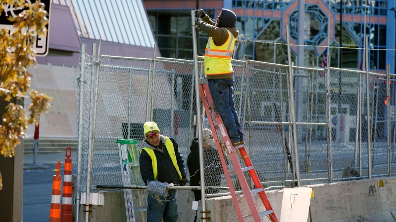 Workers install barbed wire on fencing outside the Hennepin County Government Center, Wednesday, Feb. 23, 2021 in Minneapolis, as part of security preparation for the trial of former Minneapolis police officer Derek Chauvin.  (AP / Jim Mone)