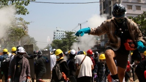 Protesters are dispersed as riot police fired tear gas behind a makeshift barricade in Yangon, Myanmar, Sunday, March 7, 2021. (AP Photo)