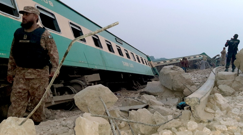 Army, police and rescue workers gather at the site of a derailed train in near Rohri, in southern Pakistan, Sunday, March 7, 2021. Eight cars of a Lahore bound train derailed in southern Pakistan early Sunday, killing and injuring some passengers, officials said. (AP Photo/Pervez Khan)