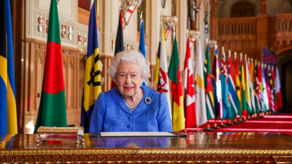In this photo made available Sunday March 7, 2021, Queen Elizabeth II poses for a photo while signing her annual Commonwealth Day Message inside St George's Hall at Windsor Castle, England, Friday March 5, 2021. (Steve Parsons/Pool via AP)