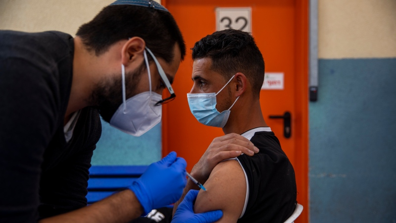 A Palestinian labourer who works in Israel receives his first dose of the Moderna COVID-19 vaccine at a coronavirus vaccination centre set up at the Meitar checkpoint crossing between Israel and the West Bank, south of the West Bank town of Hebron, Monday, March. 8, 2021. (AP Photo/Oded Balilty)