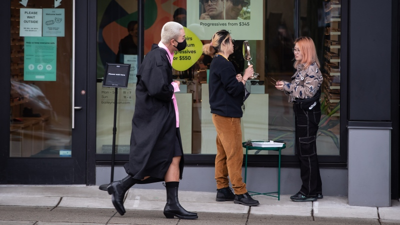 People try on eyeglasses outside a store required to limit the number of customers inside due to COVID-19, in Vancouver, on Sunday, March 7, 2021. THE CANADIAN PRESS/Darryl Dyck