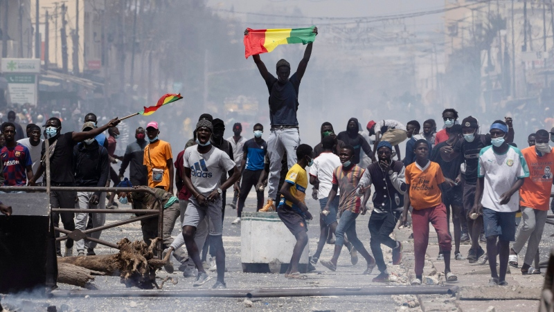 A demonstrator holds up a Senegalese flag during protests against the arrest of opposition leader and former presidential candidate Ousmane Sonko in Dakar, Senegal, Friday, March 5, 2021. Days of violent protests in Senegal have killed at least one person, local reports say, as youths take to the streets nationwide in support of the main opposition leader who was detained Wednesday. (AP Photo/Leo Correa)