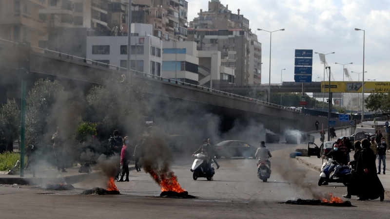 Protesters burn tires to block a road in Beirut, Lebanon, Monday, March 8, 2021. The dayslong protests intensified Monday amid a crash in the local currency, increase of consumer goods prices and political bickering between rival groups that has delayed the formation of a new government. (AP Photo/Bilal Hussein)
