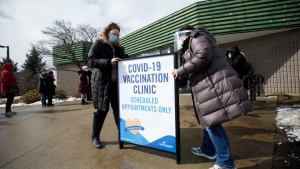 Staff install a sign as York Region residents wait in line for a COVID-19 vaccination at a mass vaccination site for residents 80 years and older, in Richmond Hill, Ont. on Monday, March 1, 2021. THE CANADIAN PRESS/Cole Burston