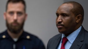 Congolese militia commander Bosco Ntaganda, right, rises as judges enter the courtroom of the International Criminal Court, or ICC, to deliver the sentence in his trial in The Hague, Netherlands, Thursday, Nov. 7, 2019. The ICC delivered the sentence on Ntaganda, accused of overseeing the slaughter of civilians by his soldiers in the Democratic Republic of Congo in 2002 and 2003. (AP Photo/Peter Dejong, Pool)
