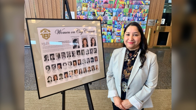 Coun. Devi Sharma poses next to a display honouring the women who have been elected to Winnipeg city council in the past century on March 8, 2021. (CTV News Photo Scott Andersson).