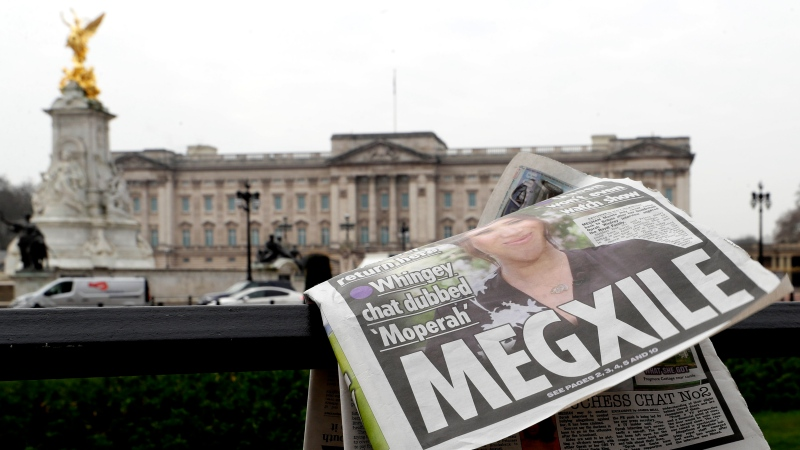 A newspaper is blown by the wind after it is placed on a railing by a television crew outside Buckingham Palace in London, Monday, March 8, 2021. (AP Photo/Kirsty Wigglesworth)