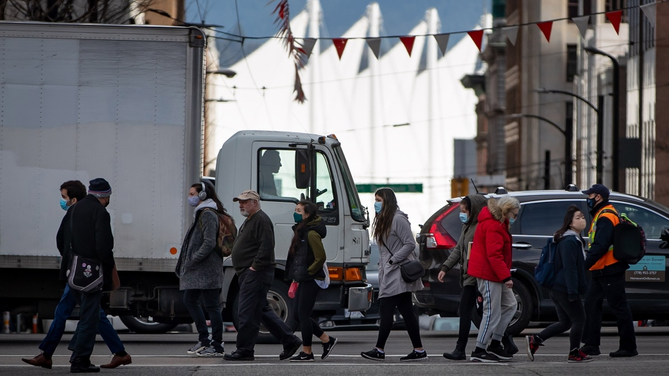 Pedestrians wearing face masks to curb the spread of COVID-19 cross a street in Vancouver, on Monday, March 8, 2021. (THE CANADIAN PRESS / Darryl Dyck)