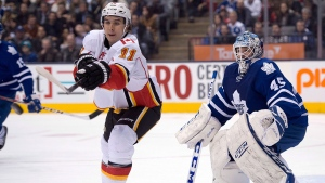 Calgary Flames centre Mikael Backlund (11) seen here trying to deflect the puck in front of Toronto Maple Leafs goaltender Jonathan Bernier in a 2014 game, has partnered with Parachutes for Pets to start a charity named after his dog Lilly, who died of cancer in January, 2021. (Frank Gunn / THE CANADIAN PRESS)