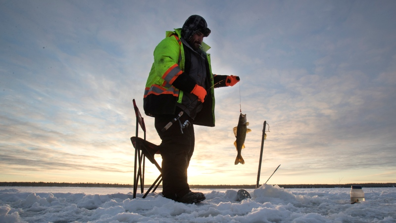 FILE - An angler from Curve Lake First Nations bring in the dawn, ice fishing on Pigeon Lake in central Ontario's Kawartha Lakes, Sunday January 24, 2021. THE CANADIAN PRESS/Fred Thornhill