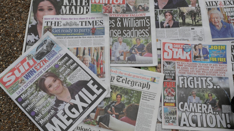 Newspapers are placed on the ground placed by a television crew in front of Buckingham Palace in London, Monday, March 8, 2021. (AP / Kirsty Wigglesworth)
