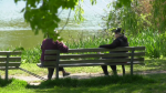 Two people speak from opposite ends of a park bench in Vancouver, B.C., during the COVID-19 pandemic.