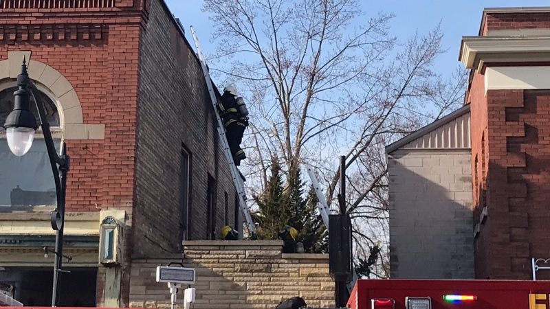 A firefighter ascends a ladder to the roof of a building where one unit was heavily damaged following a fire in West Lorne, Ont., Wednesday, March 10, 2021. (Sean Irvine / CTV News)