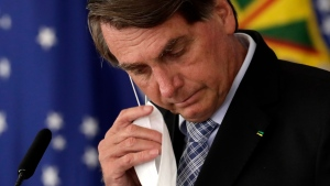 Brazilian President Jair Bolsonaro removes his mask worn due to the COVID-19 pandemic to address a ceremony to sign a law that expands the federal government's ability to acquire vaccines, at Planalto presidential palace in Brasilia, Brazil, Wednesday, March 10, 2021. (AP Photo/Eraldo Peres)