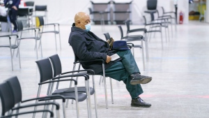 A man waits after receiving his COVID-19 vaccine at a vaccination clinic in a hockey arena in Montreal, on Wednesday, March 10, 2021. THE CANADIAN PRESS/Paul Chiasson