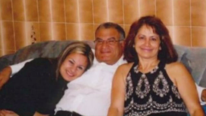 A man sitting with two women on a couch