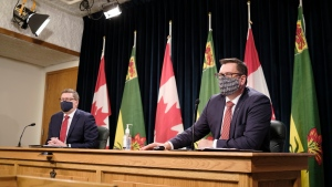 Saskatchewan Health Minister Paul Merriman, right, speaks while Premier Scott Moe looks on during a COVID-19 media update at the Legislative Building in Regina on Wednesday Dec. 9, 2020. THE CANADIAN PRESS/Michael Bell