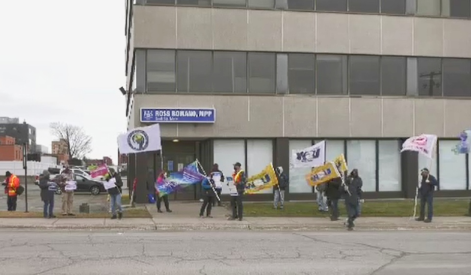 The Sault Ste Marie District Labour Council and the Ontario Confederation of University Faculty Associations gathered with other union reps in front of MPP Ross Romano's Sault Ste Marie office on Thursday. (Photo from video)