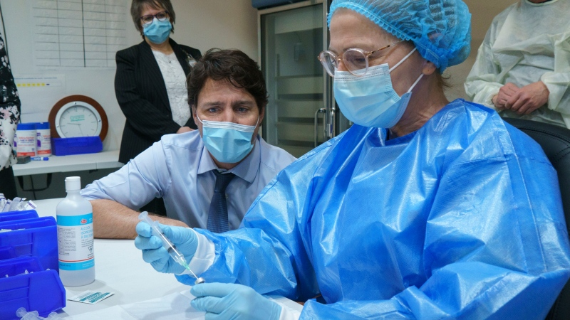 Prime Minister Justin Trudeau watch as a COVID-19 vaccine syringe is prepared as he tours a vaccination clinic in Montreal, on Monday, March 15, 2021. THE CANADIAN PRESS/Paul Chiasson
