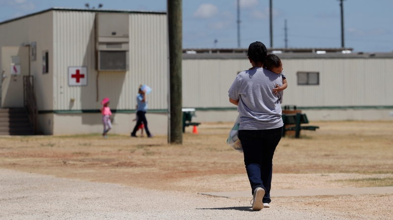 FILE - In this Aug. 23, 2019 file photo, immigrants seeking asylum walk at the ICE South Texas Family Residential Center, in Dilley, Texas.  (AP Photo/Eric Gay, File)