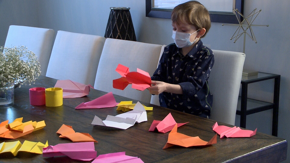 Marcus Brun, 7, shows off a few of the paper planes he's folded himself. Marcus says he's made hundreds of planes since picking up the skill last summer. (Chris Black/CTV Ottawa, March 15, 2021)