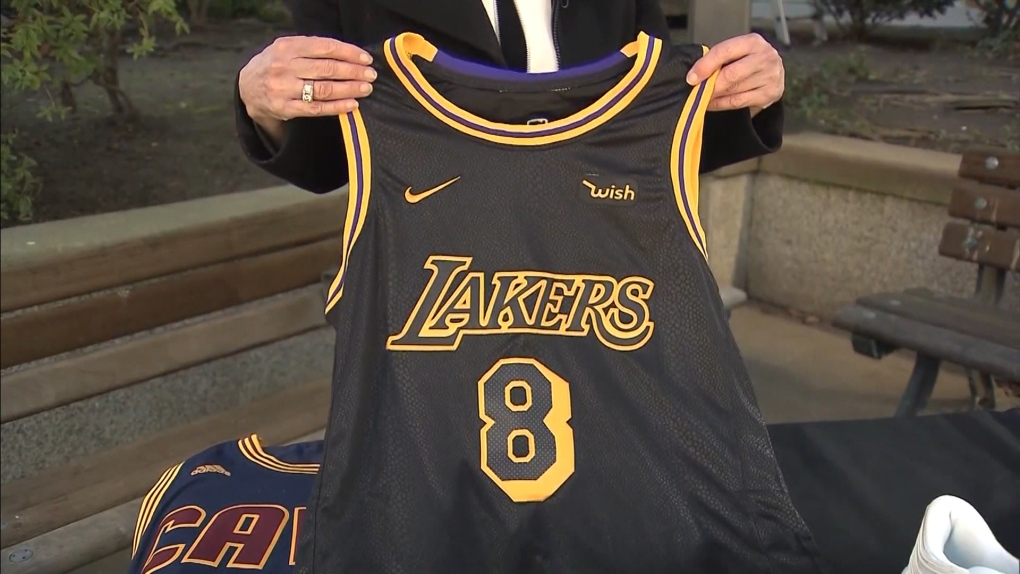 Crime Stoppers' Linda Annis holds up a fake jersey
