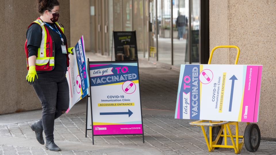 A worker sets up signs for a mass vaccination clinic in Toronto on Wednesday, March 17, 2021. THE CANADIAN PRESS/Frank Gunn