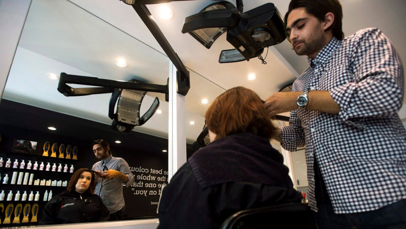 Raphael Azran, right, owner of the Colour Lab, applies a hair colouring product on Kat McCallum in Toronto on Tuesday, July 30, 2013. THE CANADIAN PRESS/Nathan Denette