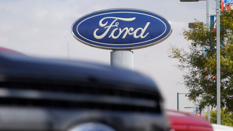 In this Sunday, Oct. 11, 2020, file photo, the company logo hangs over a row of 2020 F-150 pickup trucks at a Ford dealership, in Denver. (AP Photo/David Zalubowski, File)