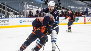 Edmonton Oilers' Tyson Barrie (22) and Winnipeg Jets' Adam Lowry (17) battle for the puck during third period NHL action in Edmonton on Thursday, March 18, 2021 (THE CANADIAN PRESS/Jason Franson).