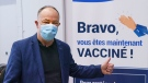 Quebec Health Minister Christian Dube gives a thumbs up as he walks past a poster after receiving the AstraZeneca Covishield vaccine at a COVID-19 vaccination clinic in Montreal, Thursday, March 18, 2021. THE CANADIAN PRESS/Paul Chiasson