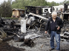 A resident of a Surrey, B.C., trailer park surveys the damages after a hot air balloon crashed into a mobile home. (CP / Richard Lam)