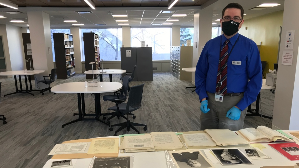 Jeremy Mohr, stands over the collection of Spanish Influenza material at the Provincial Archives of Saskatchewan. (Cally Stephanow / CTV News)
