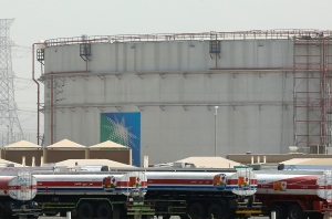 Fuel trucks line up in front of storage tanks at the North Jiddah bulk plant, an Aramco oil facility, in Jiddah, Saudi Arabia, Sunday, March 21, 2021. Saudi Arabia's state-backed oil giant Aramco announced Sunday that its profits nearly halved in 2020 to $49 billion, a big drop that came as the coronavirus pandemic roiled global energy markets. (AP Photo/Amr Nabil)
