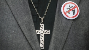 A button denouncing Bill 21 is shown on a lapel next to a crucifix during a demonstration against the bill in Montreal, Sunday, October 6, 2019.The controversial Quebec secularism law bans some public-sector employees from wearing religious symbols in the workplace. THE CANADIAN PRESS/Graham Hughes