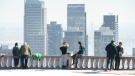 People take in the sun on a warm day while looking over the city of Montreal, on Wednesday, March 17, 2021. THE CANADIAN PRESS/Paul Chiasson