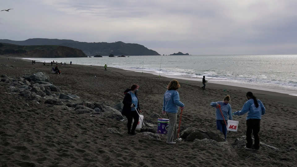Pacifica Beach Coalition volunteers Iona Pratt-Bauman, from left, Anneliese Phillips, Sophia Woehl and Amaelia Bringas, all 16, pick up trash off Sharp Park Beach in Pacifica, Calif., Wednesday, March 17, 2021. (AP Photo/Jeff Chiu)
