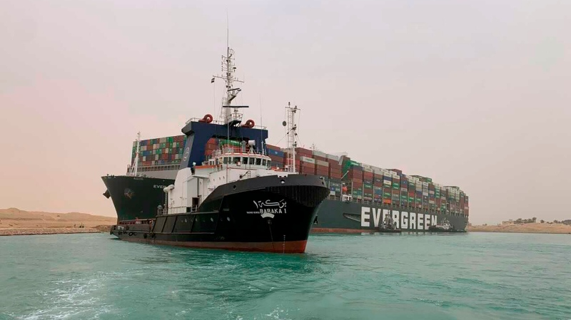 In this photo released by the Suez Canal Authority, a boat navigates in front of a massive cargo ship, named the Ever Green, rear, which is operated by the Taiwan-based firm Evergreen, as it sits grounded Wednesday, March 24, 2021, after it turned sideways in Egypt's Suez Canal, blocking traffic in a crucial East-West waterway for global shipping. (Suez Canal Authority via AP)