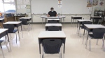 A teacher sits in an empty B.C. classroom during the COVID-19 pandemic.