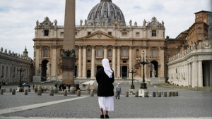 A nun stands in St. Peter's Square at the Vatican, Sunday, March 21, 2021. (AP Photo/Gregorio Borgia)