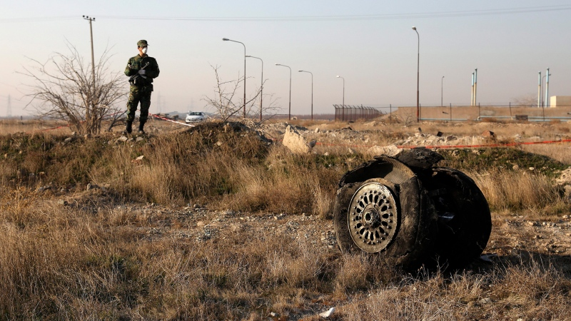 A police officer stands guard as debris is seen from an Ukrainian plane which crashed in Shahedshahr, southwest of the capital Tehran, Iran, January 8, 2020. THE CANADIAN PRESS/AP, Ebrahim Noroozi