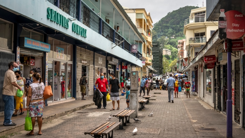 Pedestrians wear masks as they walk on a street in the capital Victoria, Mahe Island, Seychelles Thursday, Feb. 25, 2021. (AP Photo/Salim Ally)