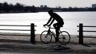 A cyclist makes their way along the edge of Dow's Lake in Ottawa on Tuesday, March 23, 2021. (Sean Kilpatrick/THE CANADIAN PRESS)