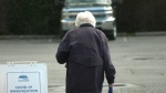 A senior is seen walking through Esquimalt's COVID-19 immunization clinic at the Archie Browning Sports Centre: March 25, 2021 (CTV News)